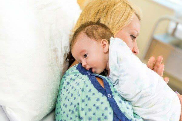 Đặt bé lên vai và vuốt nhẹ lưng khi trẻ sơ sinh bị đầy bụng